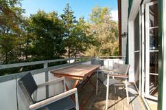 Mit Holzdielen belegter Süd-West-Balkon, der mit bequemen Balkonstühlen und Tisch zum Verweilen einlädt.
