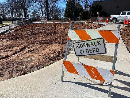 """A sign reading """"sidewalk closed"""" blocks the sidewalk near the church"""