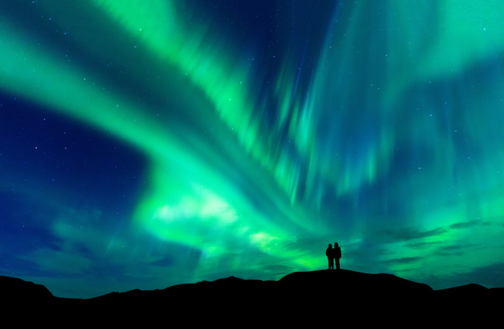Couple watching Iceland Northern Lights is one of the best things to do