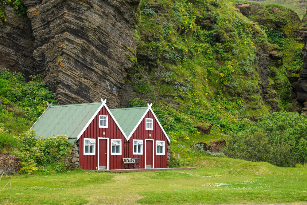 Campervan rental in Iceland at campsite with red houses