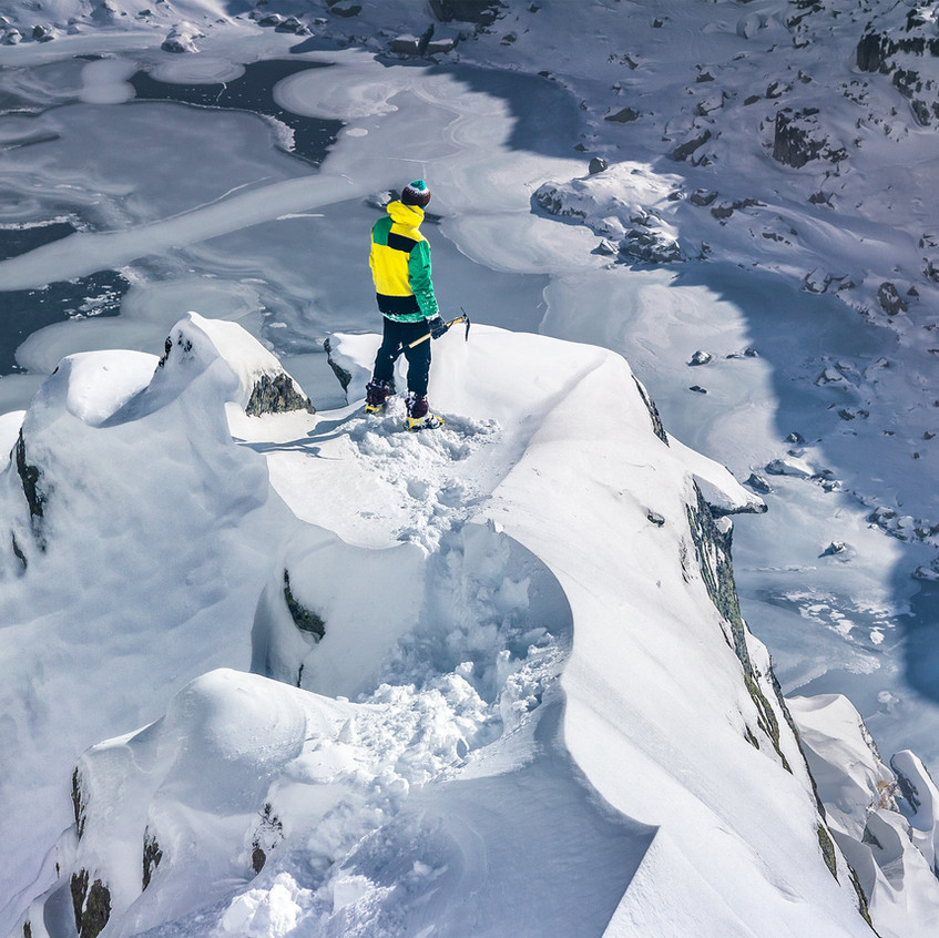 Man on top of a snowy mountain top