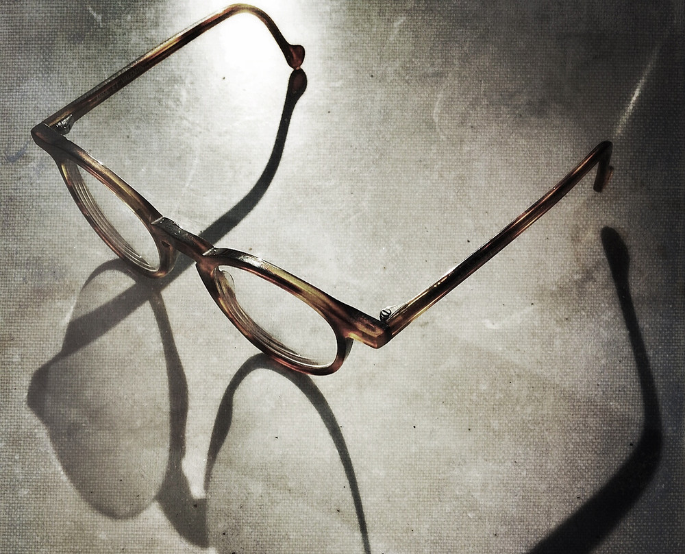A pair of glasses on a steel or stone table.