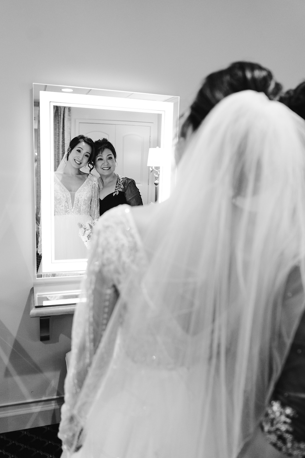 black and white photo of the bride with her mother looking in the mirror