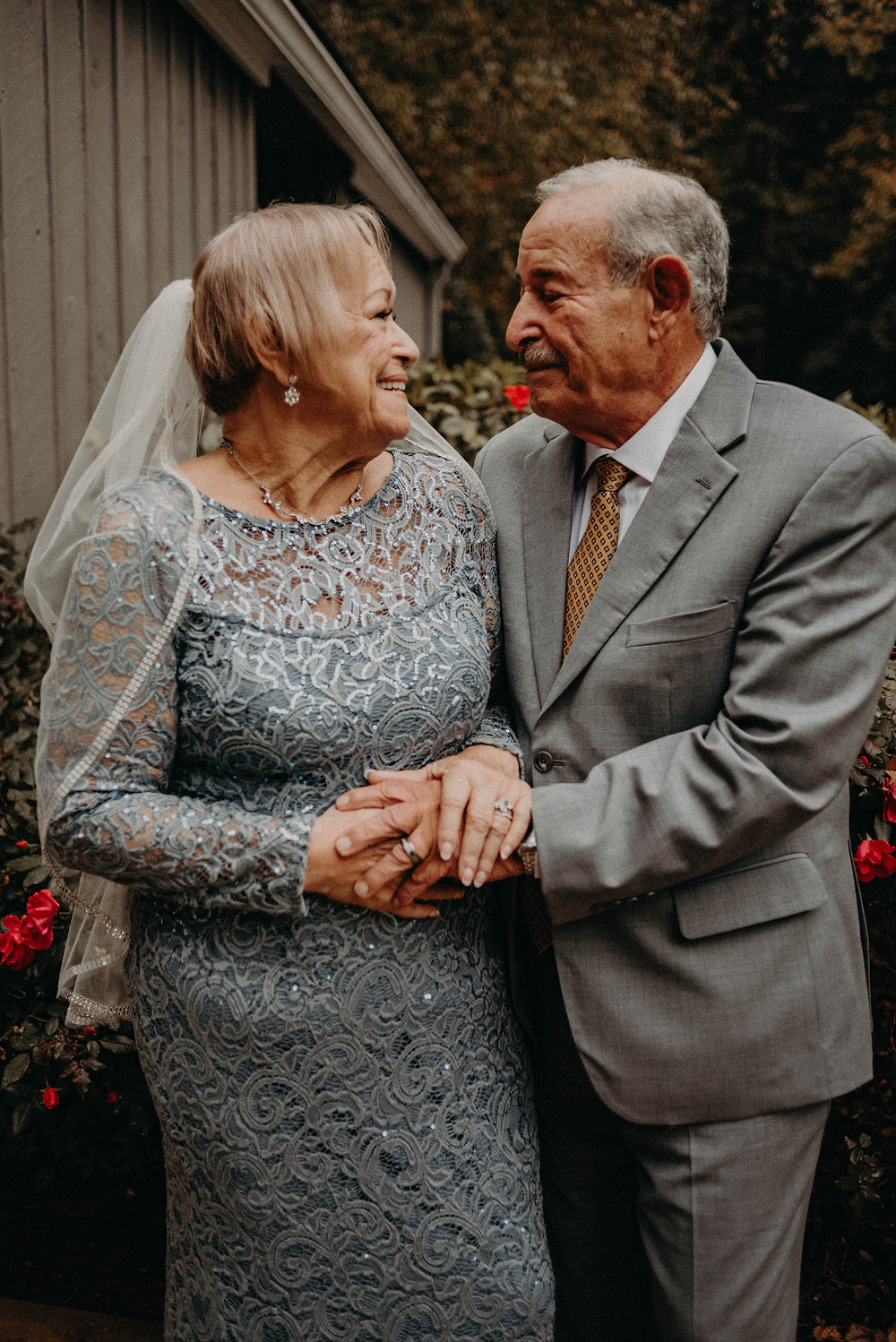 Elderly couple smiling at each other at their wedding