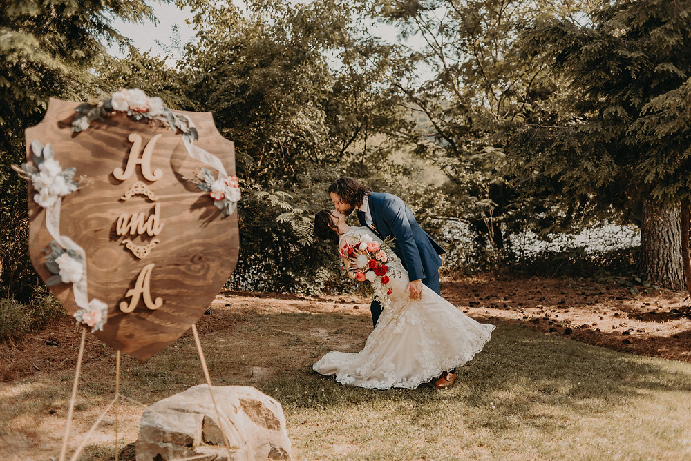 Bride and Groom kissing after the ceremony outdoors with a sign