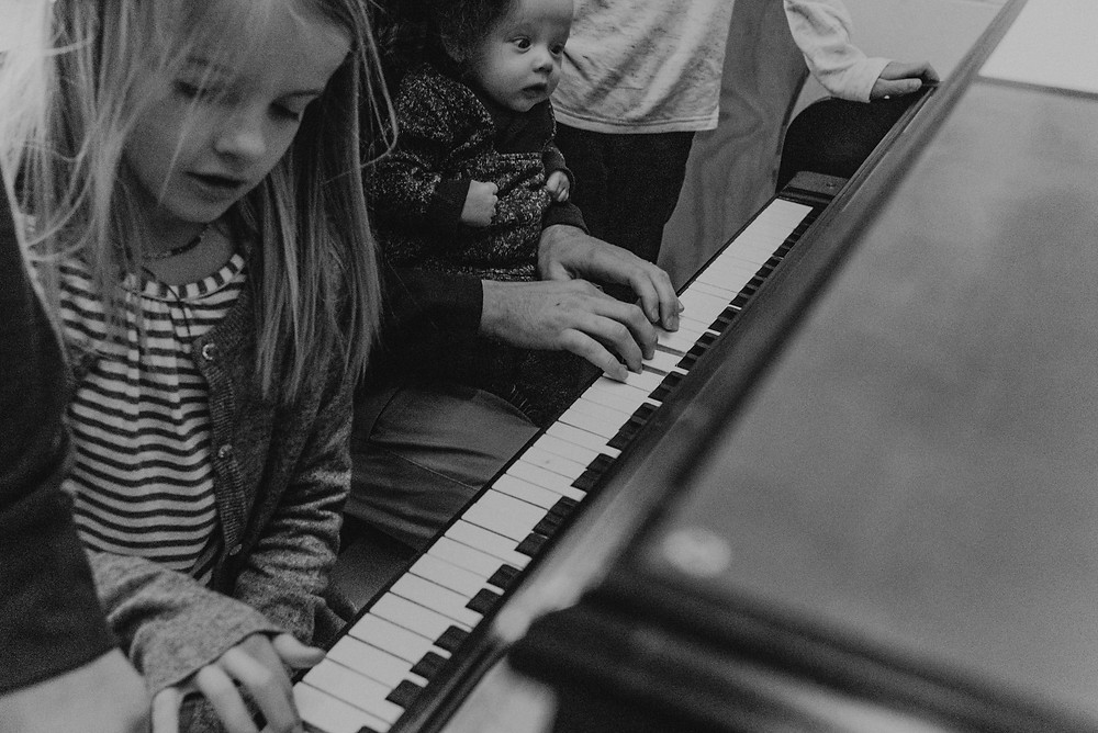 Black and white portrait of children playing the piano
