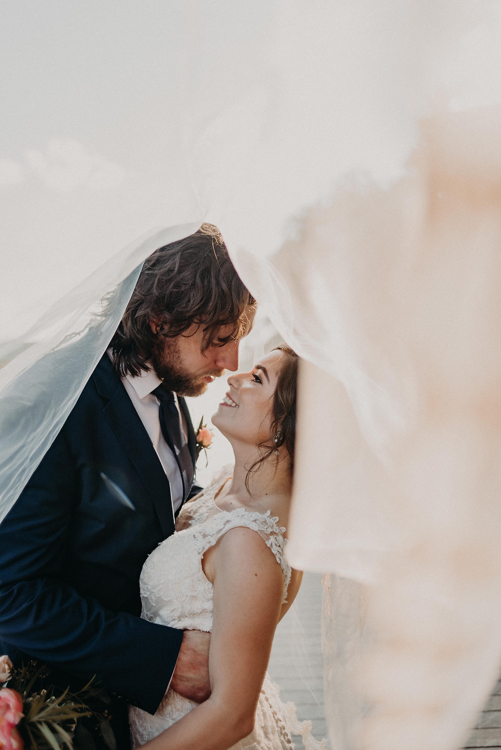Couple smiling at each other under the veil