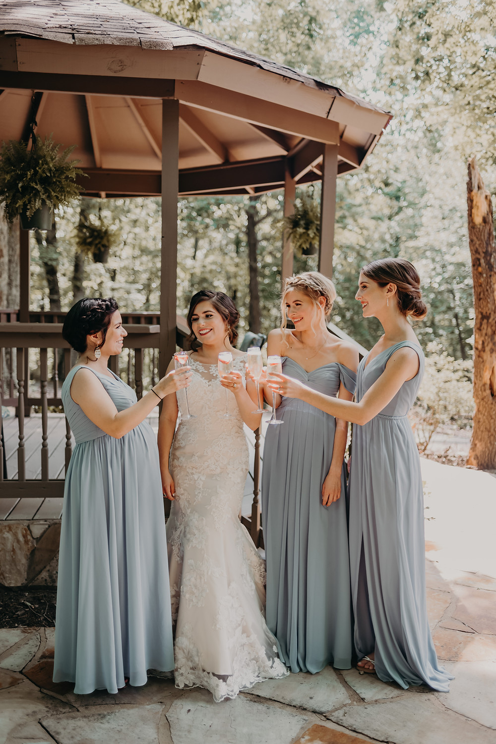 Bride in a lace dress with her bridesmaids with blue dresses