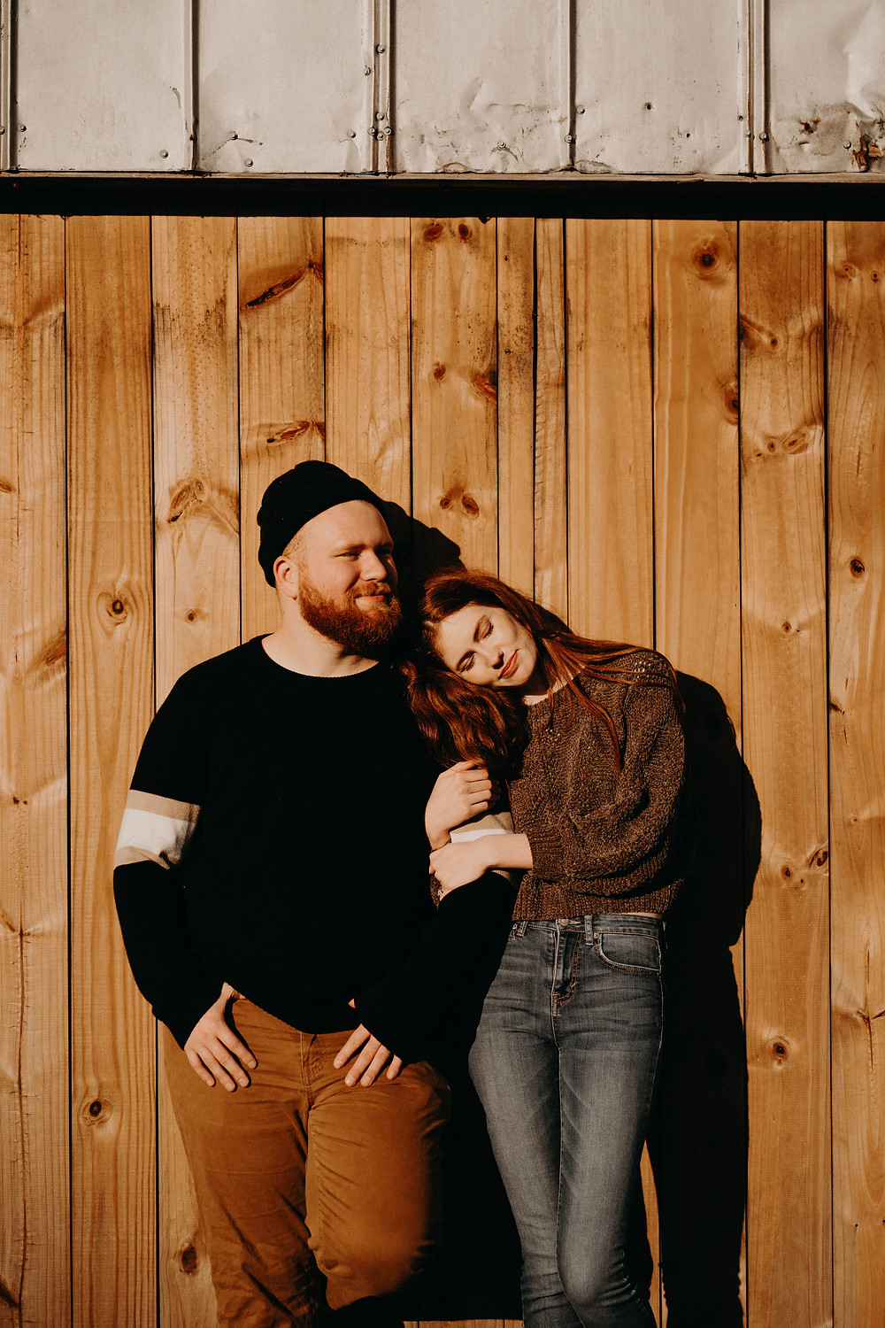 ginger couple wearinf fall clothes in a wood wall