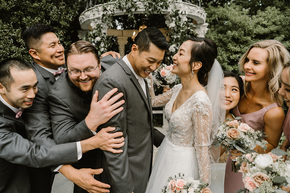 asian couple posing with their wedding party