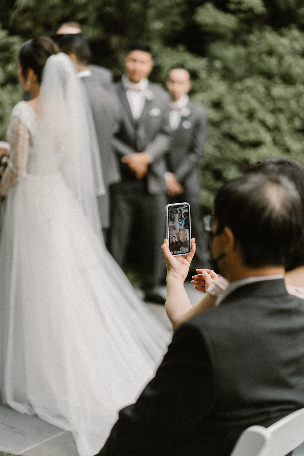 guest filming wedding ceremony with his phone