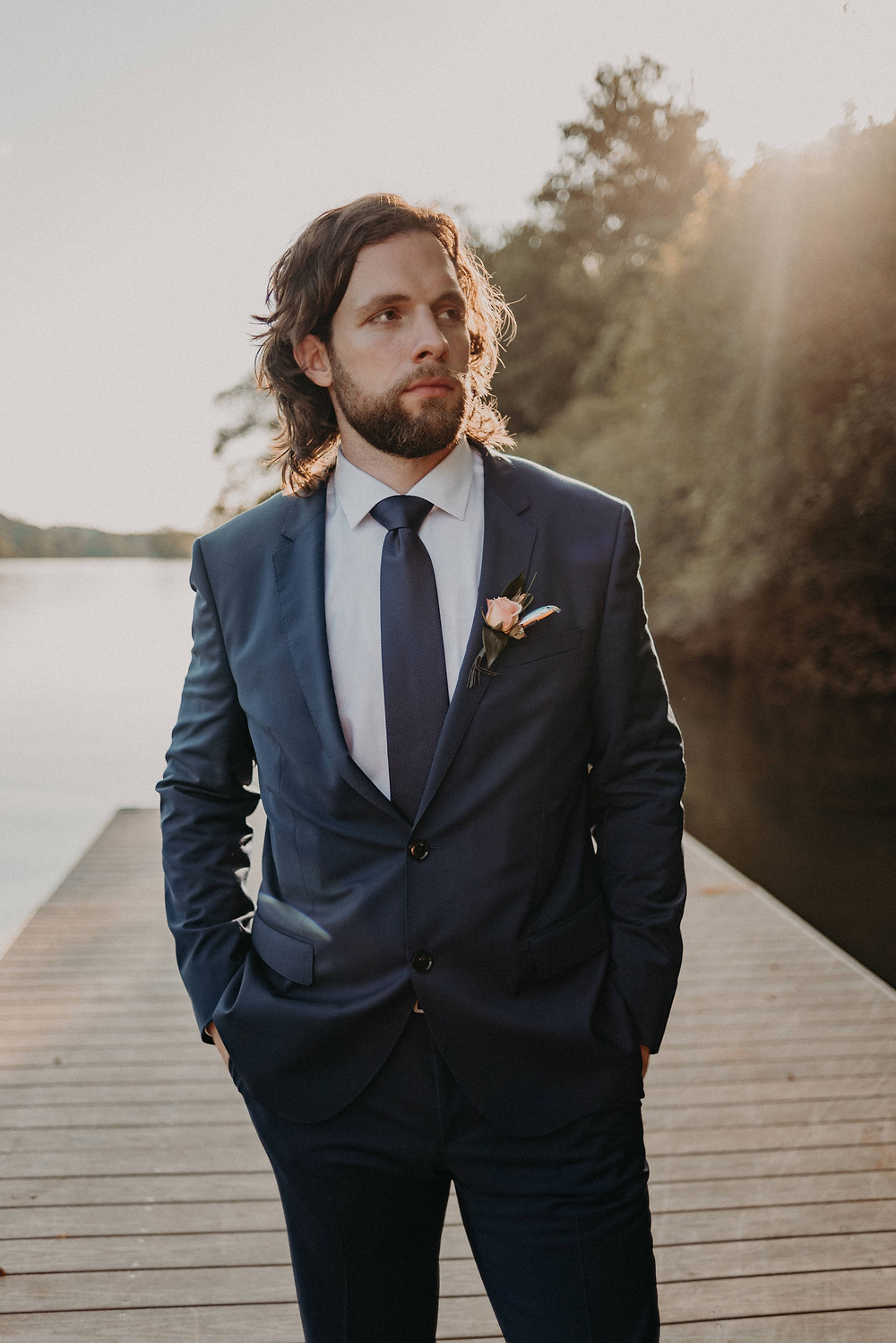 Groom in a beautiful suit by the river