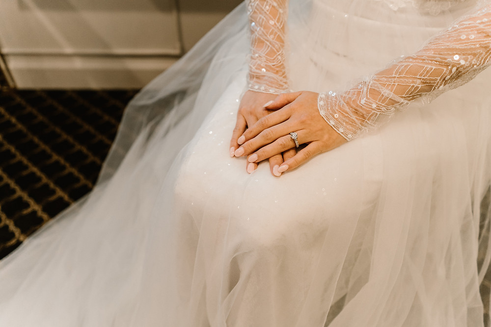 bride's hand with diamond ring. Tulle wedding dress