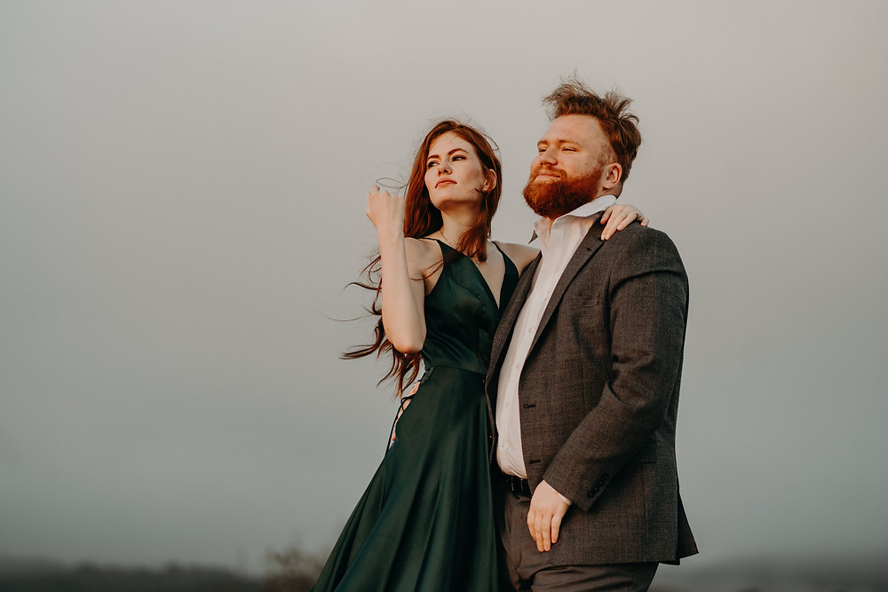 Adventure engagement photoshoot. Ginger couple wearing formal clothes at the mountain
