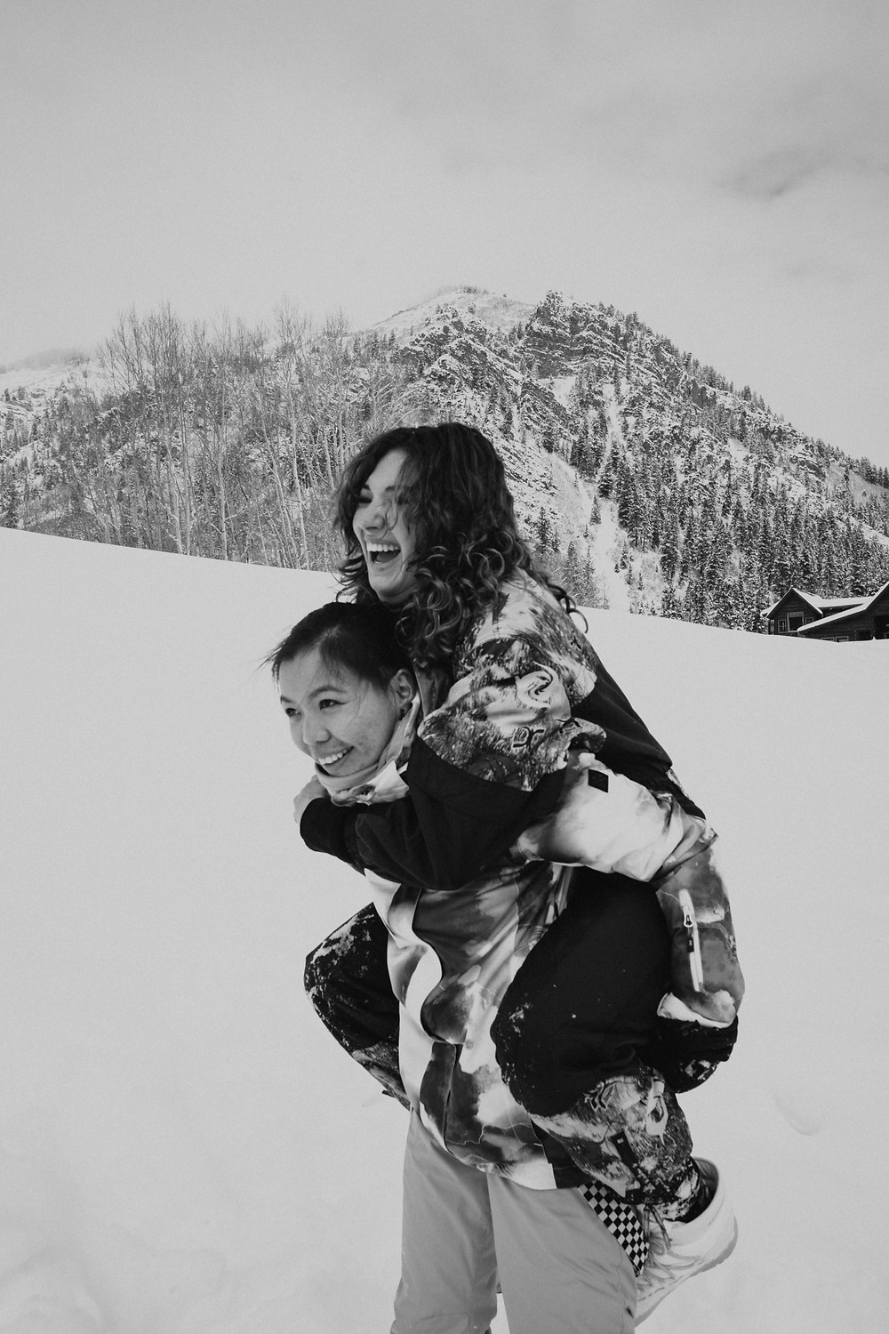 black and white photo of couple having fun in the snow
