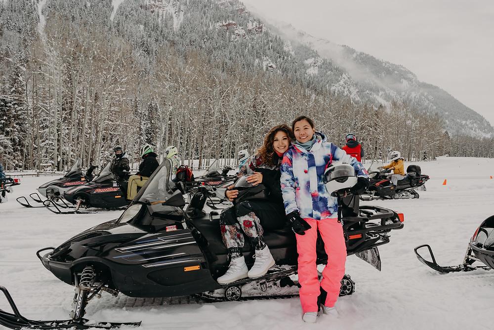 couple in a snowmobile in aspen co