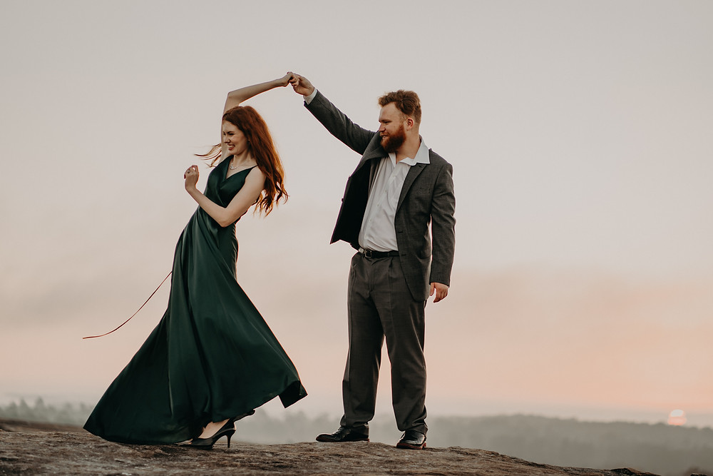red-haired couple dancing and laughting at the top of the mountain at sunrise