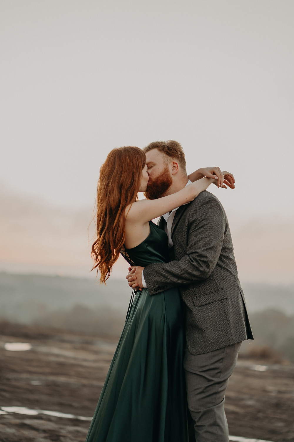red-haired bride wearing a long green satin dress and groom in a suit kissing on top of the mountain at dawn