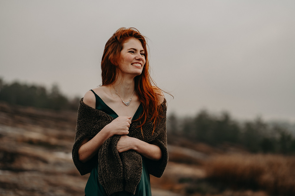 red-haired bride smiling at the mountain at sunrise