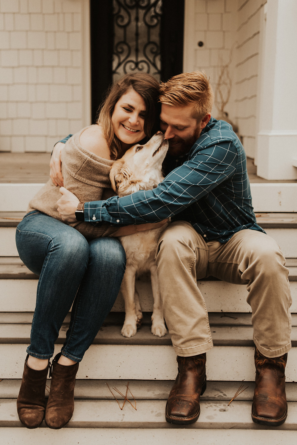 couple giving their dog a hug in front of their house