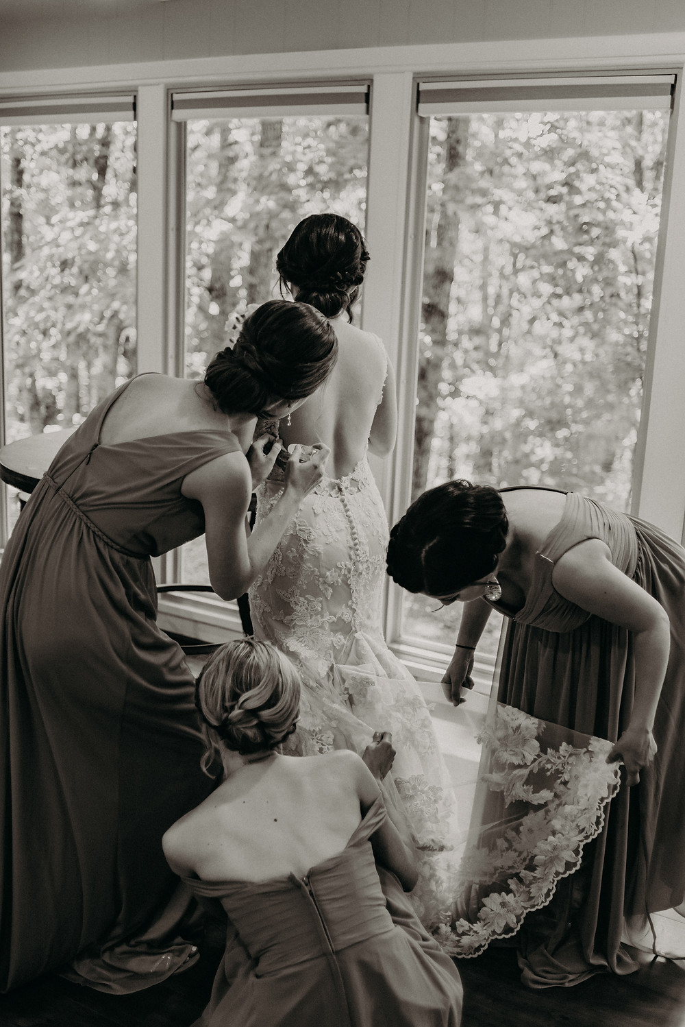 Black and white photo of bride getting ready for the wedding with her bridesmaids