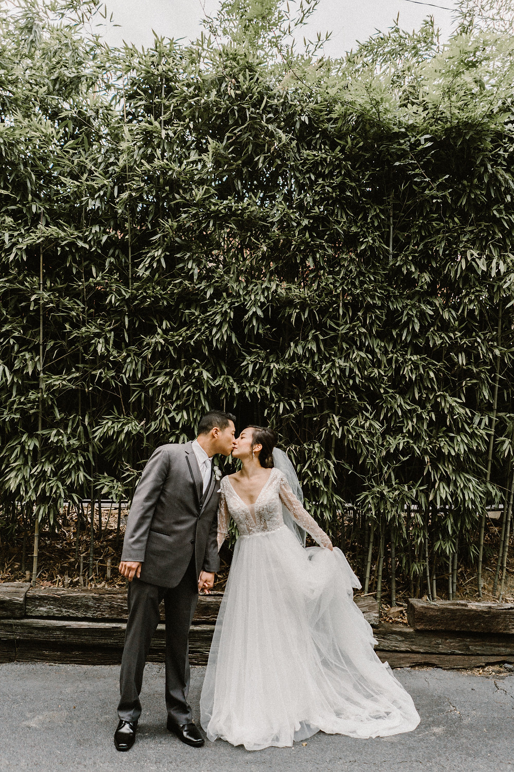 asian couple kissing in a garde. Tulle wedding dres and gary suit