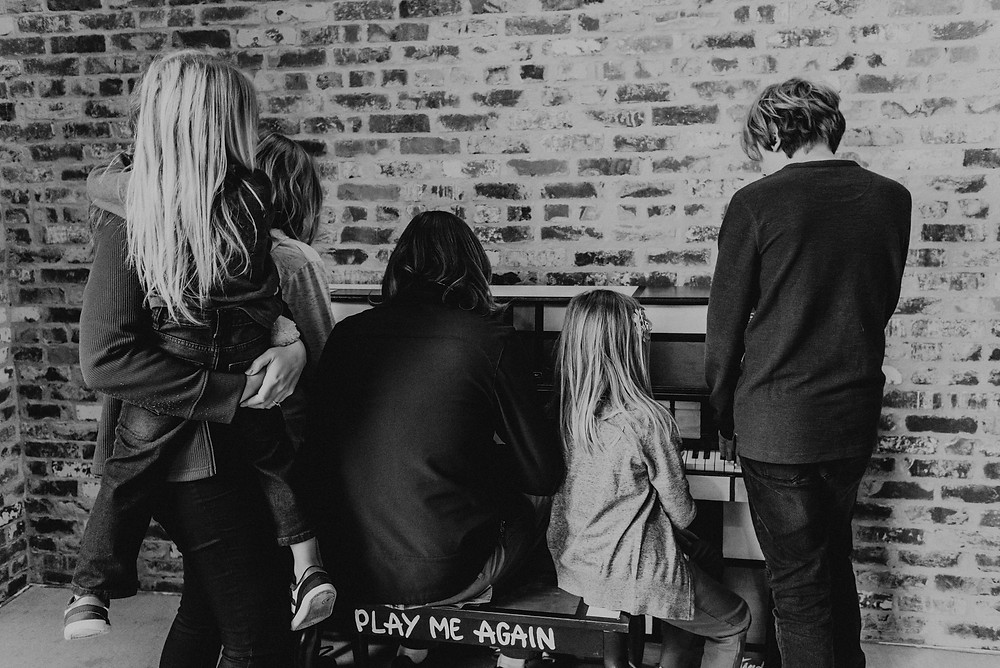 Black and white portrait of family playing the piano