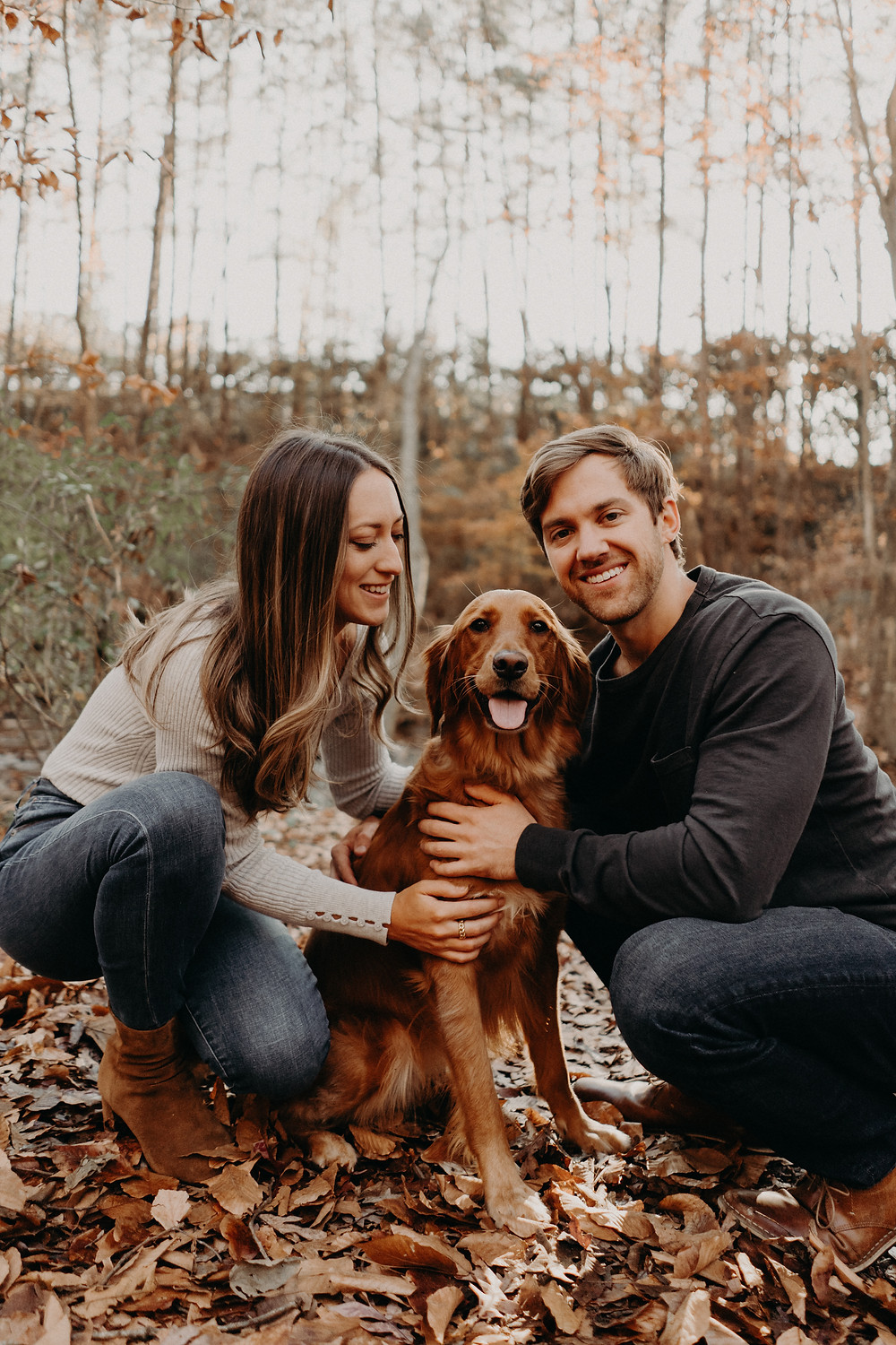 Couple with their dog posing in a fall photo session
