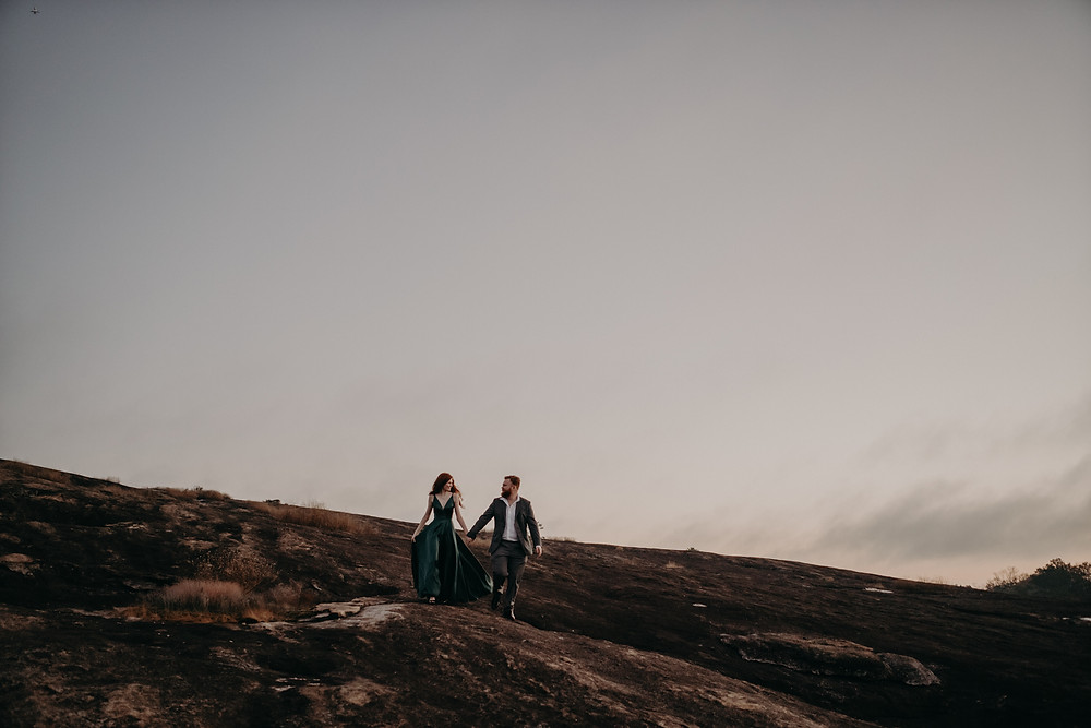 red-haired bride and groom holding hands walking on the mountain at dawn
