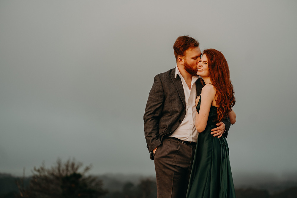 red-haired couple smiling and hugging wearing formal clothes at the mountain