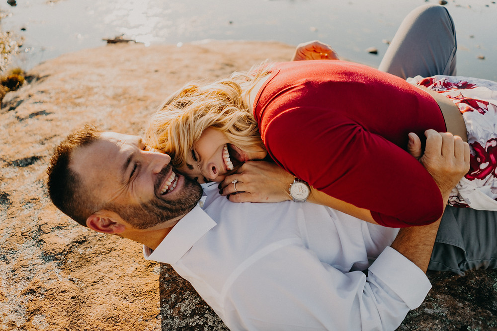 Couple hugging and laughing at their engagement session photographed by Nathalia Frykman