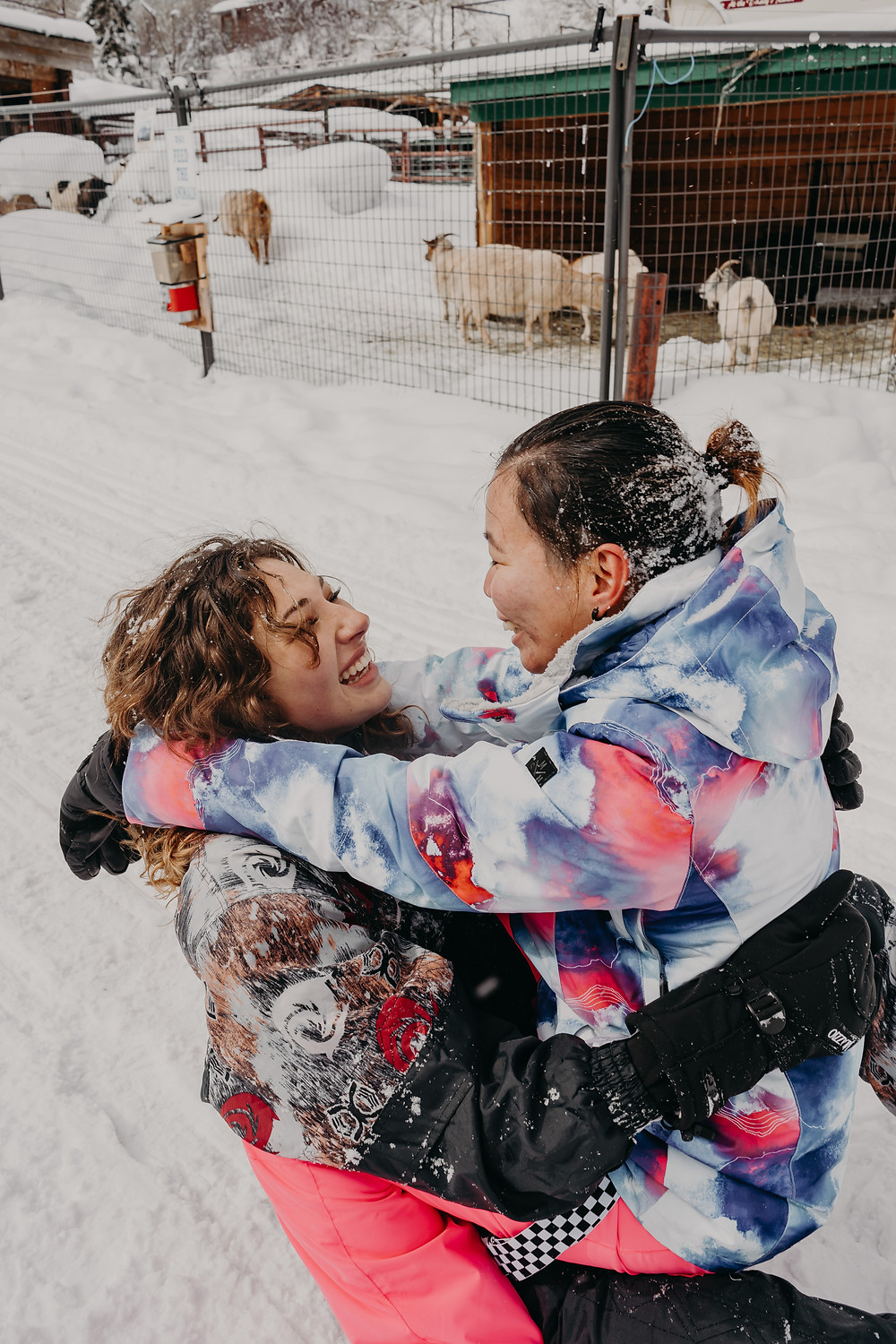 lesbian couple playing in the snow