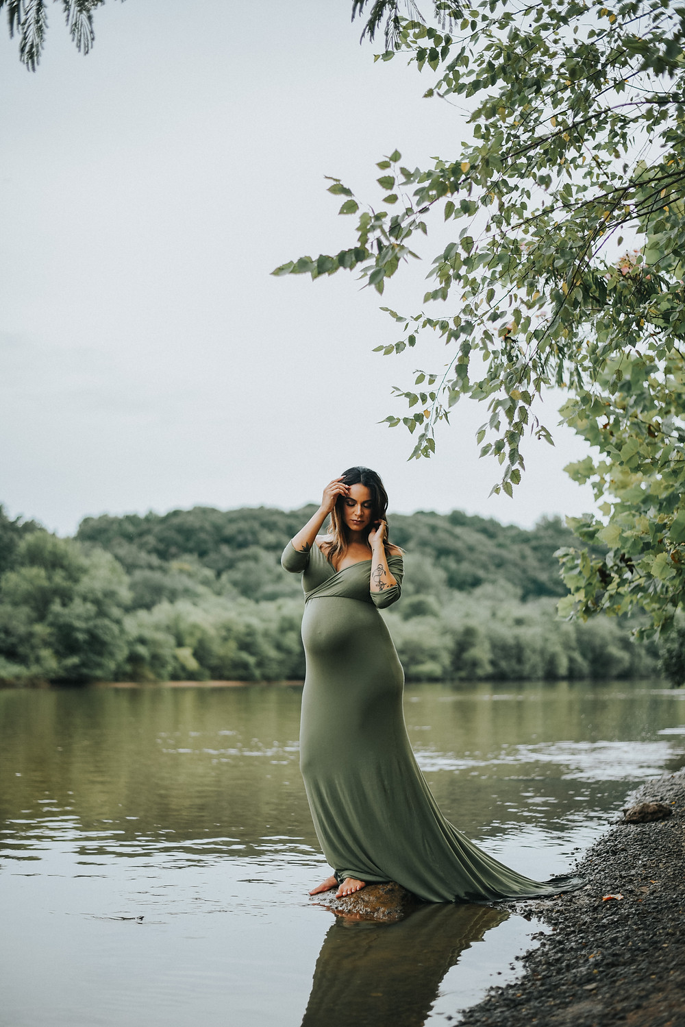 pregnant woman in a green dress by the river