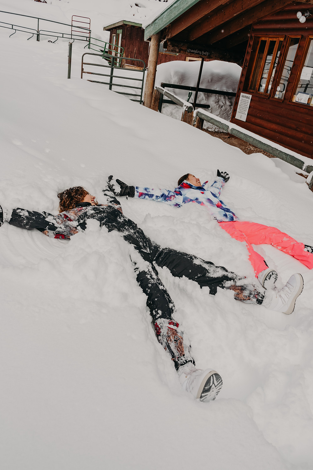 couple making snow angels in colorado