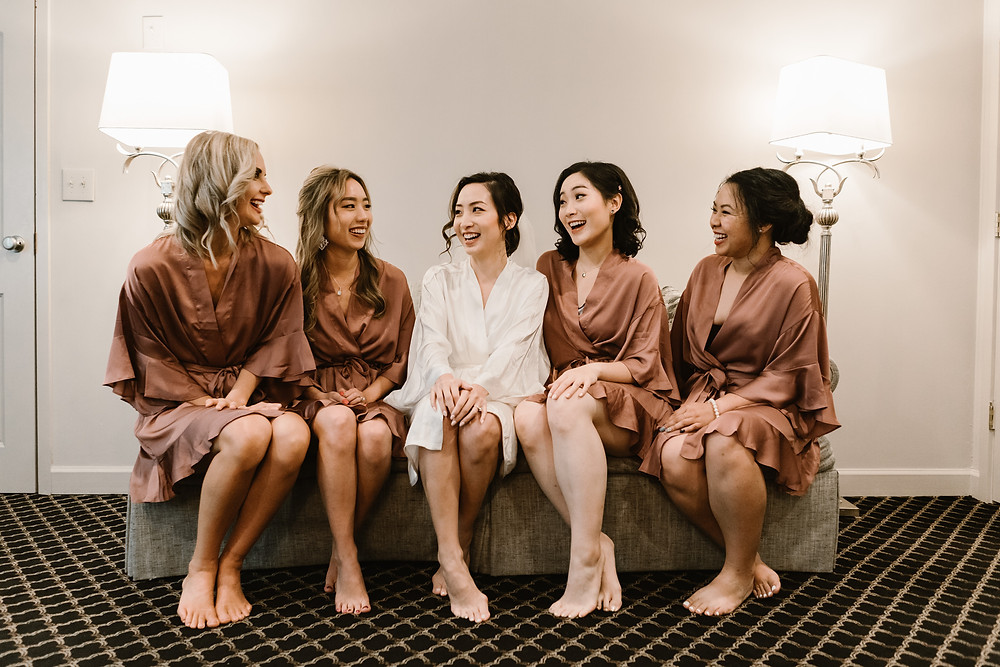 bride wearing white silk clothes with her bridesmaids wearing nude silk robes.