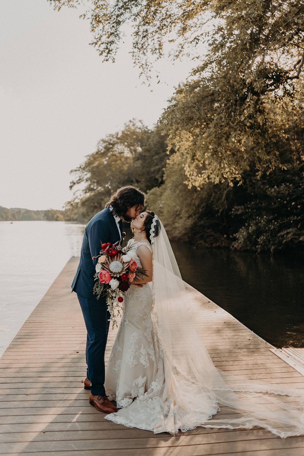 Bride and Groom kissing by the river