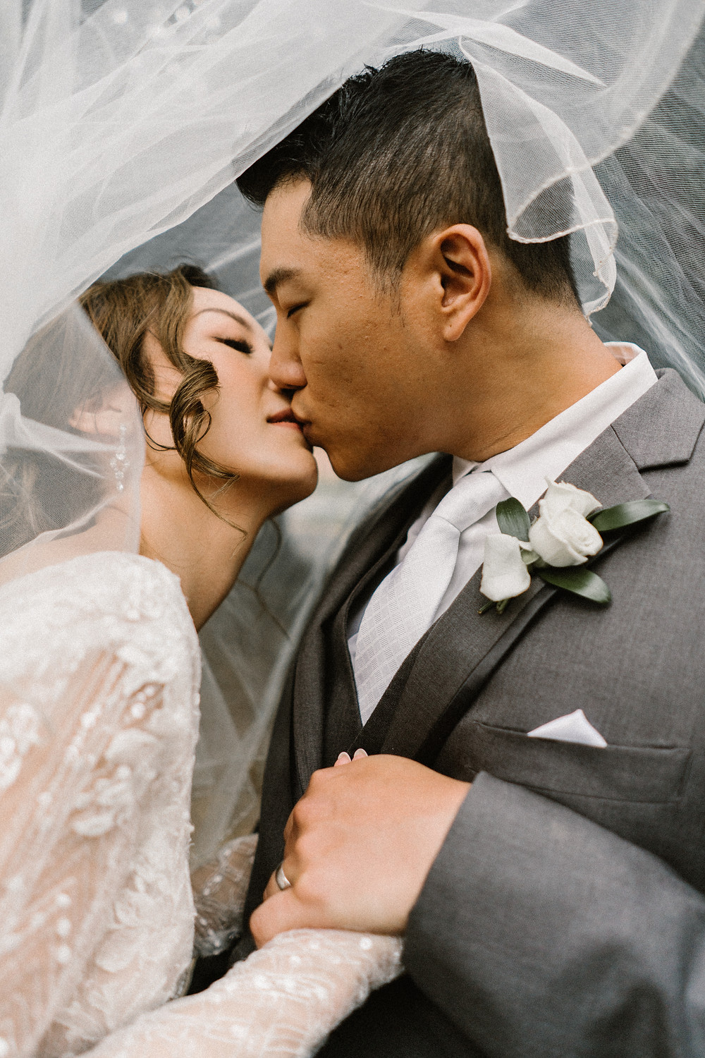 asian couple kissing under the bride's veil
