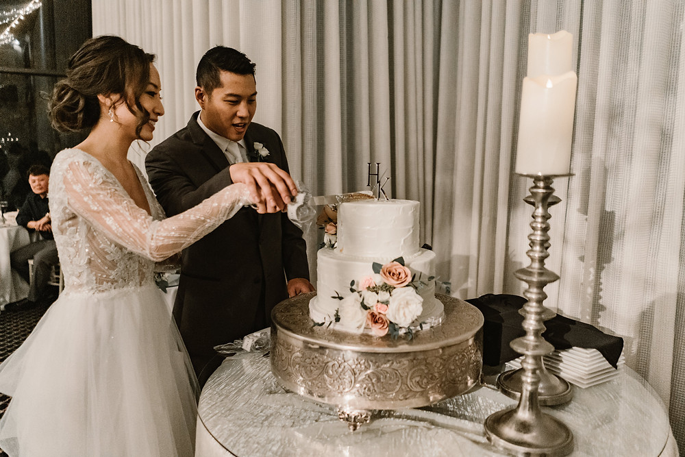 asian bride and groom cutting their wedding cake