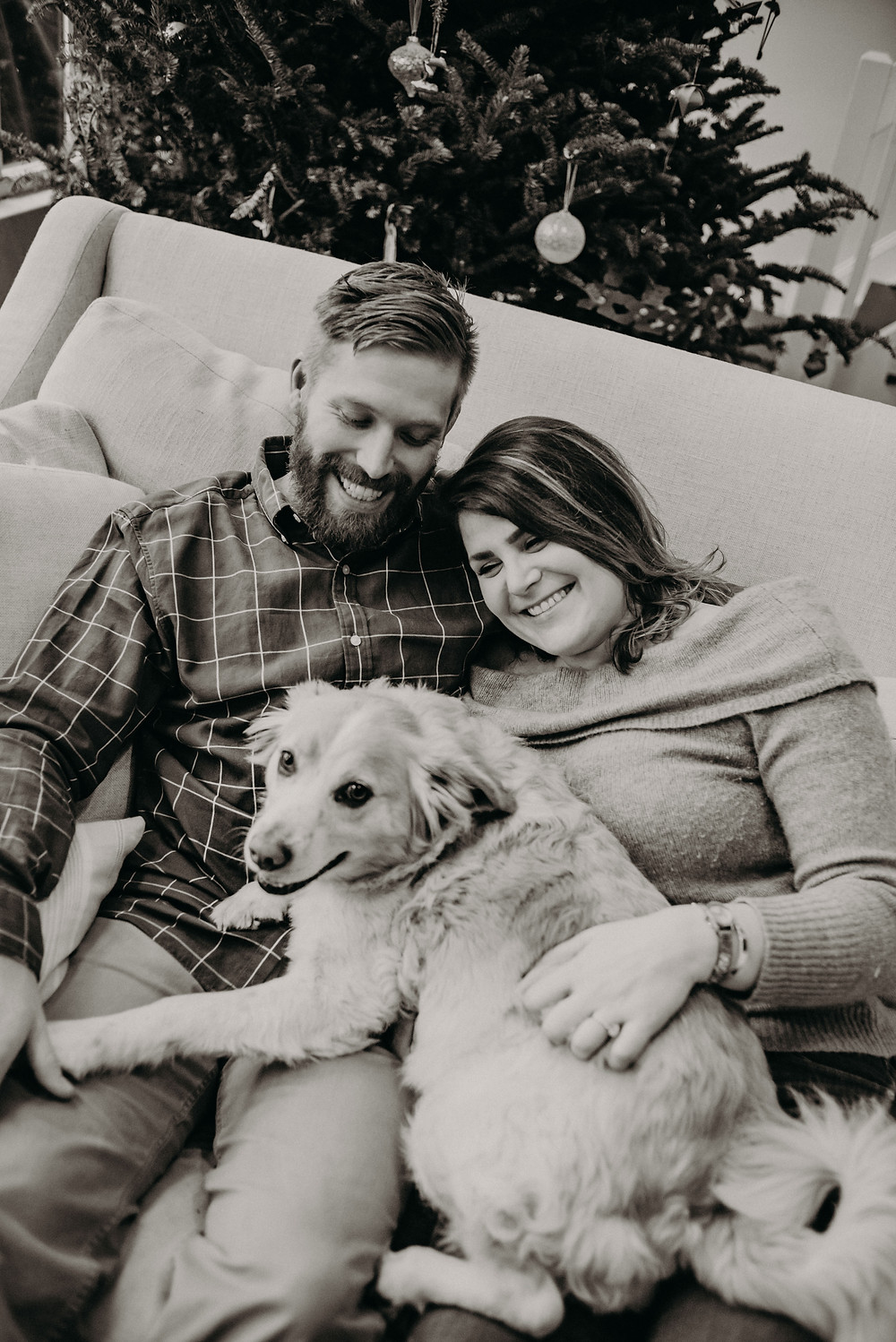 black and white photo of a couple and their dog in the sofa