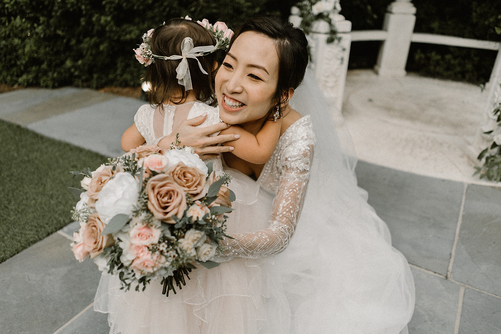 Bride hugging her flower girl. Tulle dresses and rose and white flowers