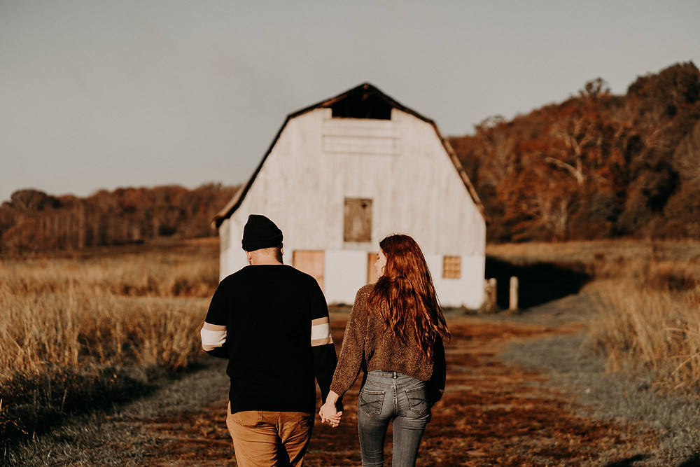 ginger couple holding hands in front of a barn