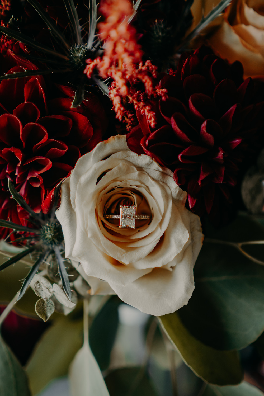 engagement ring in a bouquet with white and red flowers