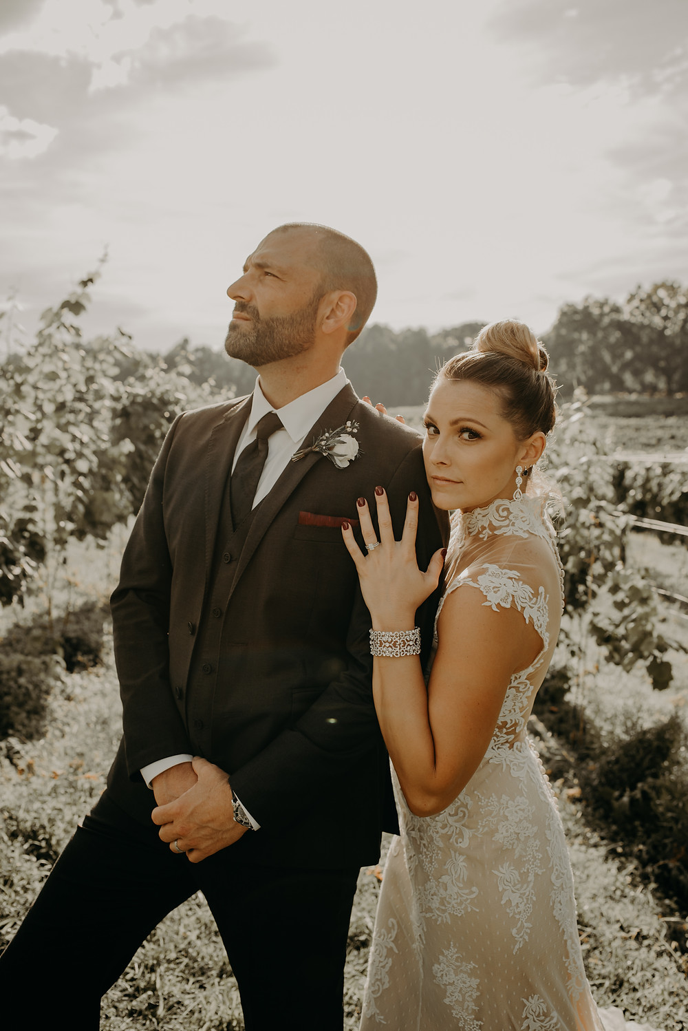 bride wearing a lace dress with her groom wearing a black suit in a vineyard
