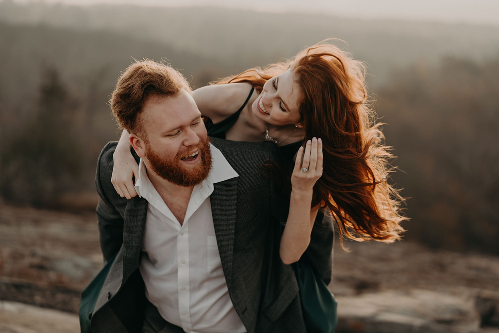 red-haired groom giving his red-haired bride a piggy back ride