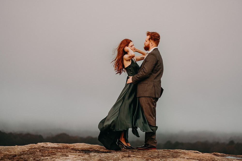 Red-haired bride and groom in formalwear high up on the mountain at sunrise