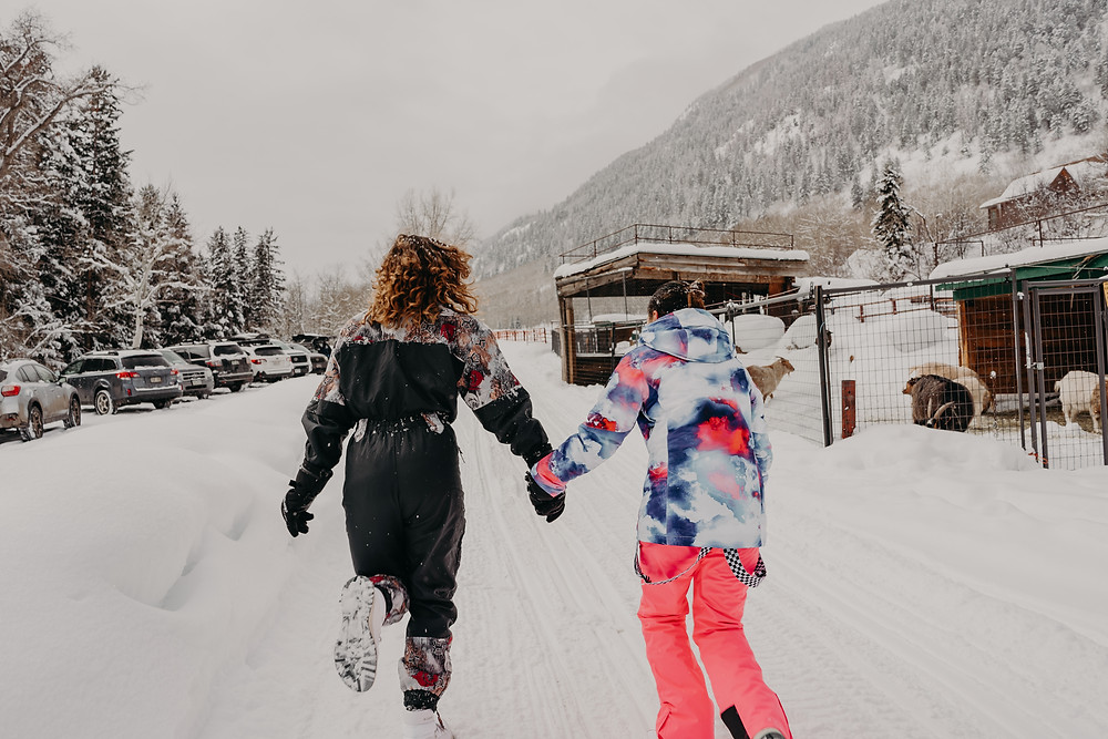 couple running in the snow holding hands