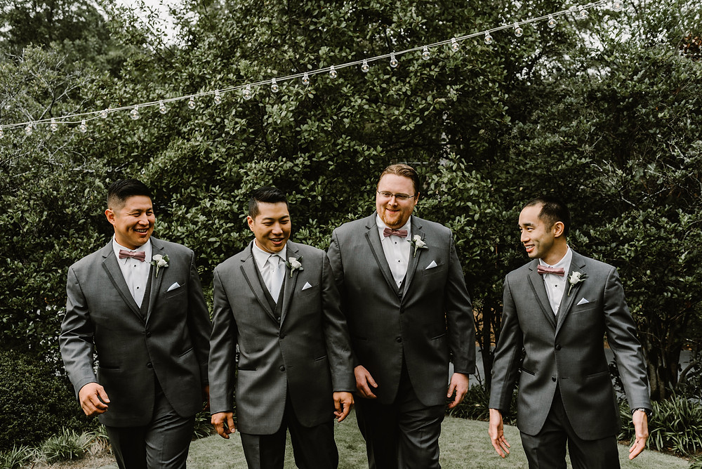 groom and groonsmen wearing gray suits in a garden