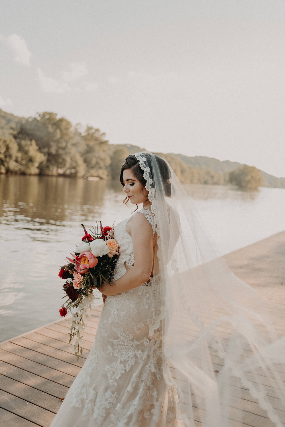 Beautiful bride in a lace dress and colorful bouquet by the river
