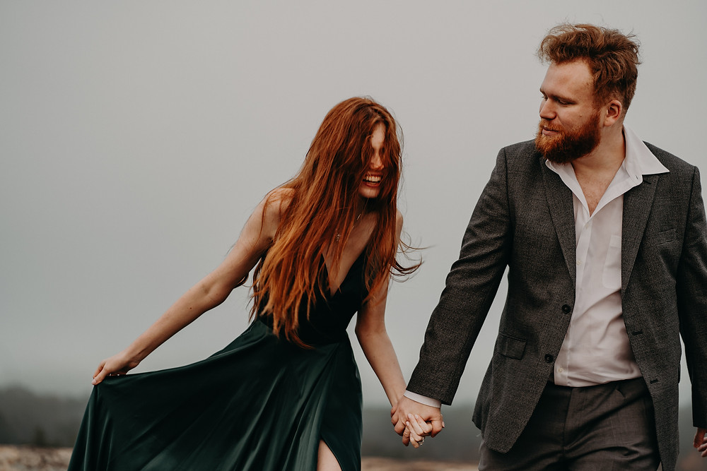 red-haired couple in formal clothes holding hands at the mountain