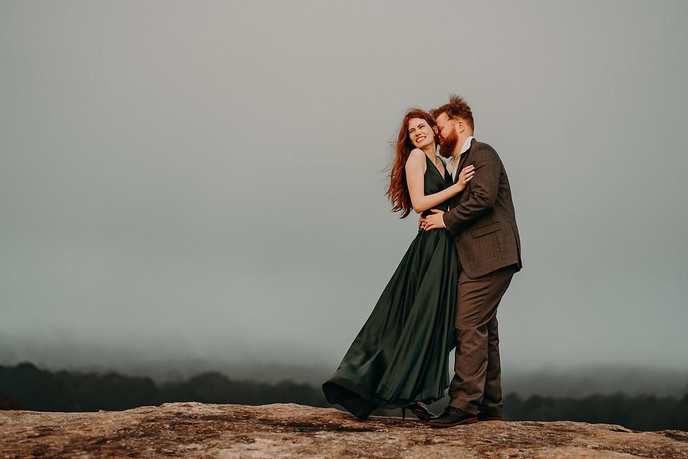 Sunrise front lit engagement photo. Ginger bride wearing a long green satin dress hugging the groom